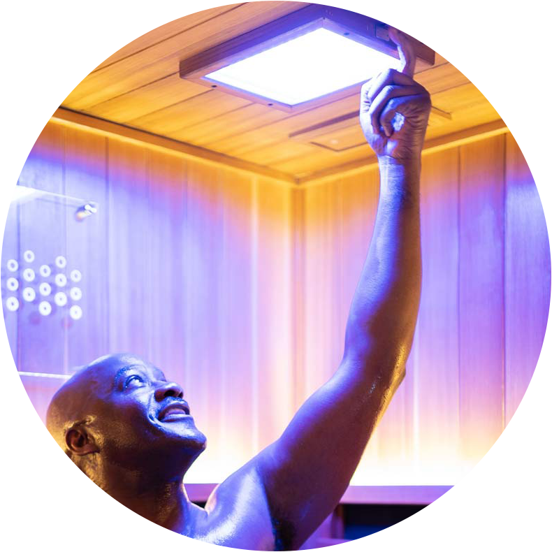 man using color light therapy inside of sauna